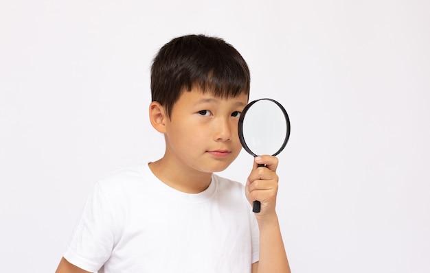 子供の発達、教育の概念。虫眼鏡のループ、クローズアップを通して見ている子供