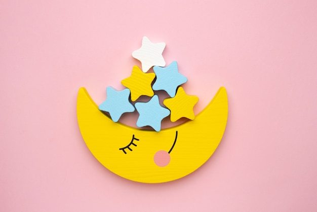 Children developmental toy for the development of motor skills, a crescent moon with stars balancer, on a pink background top view