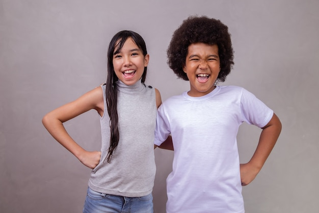 Children of different diversity on gray background. japanese girl with an afro child on gray background with space for text.
