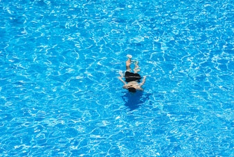 Children diving in a pool in summer