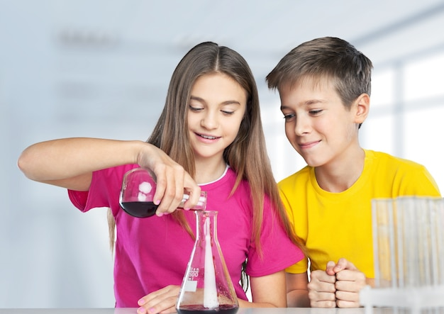 Children doing chemical experiment with glass tubes