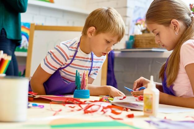 学校で手作りの工芸品をしている子供たち
