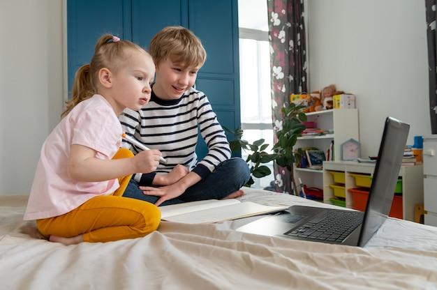 집에서 노트북을 사용하여 숙제를하는 어린이