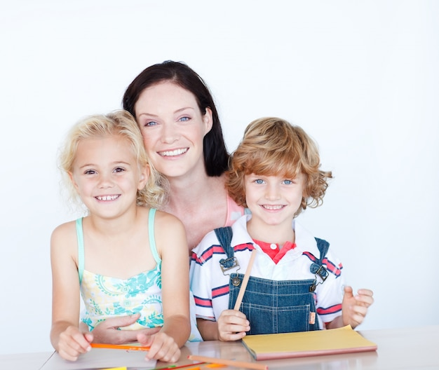 Children doing homework with their mother smiling at the camera