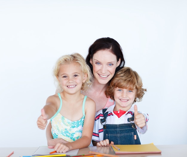 Children doing homework with their mother with thumbs up