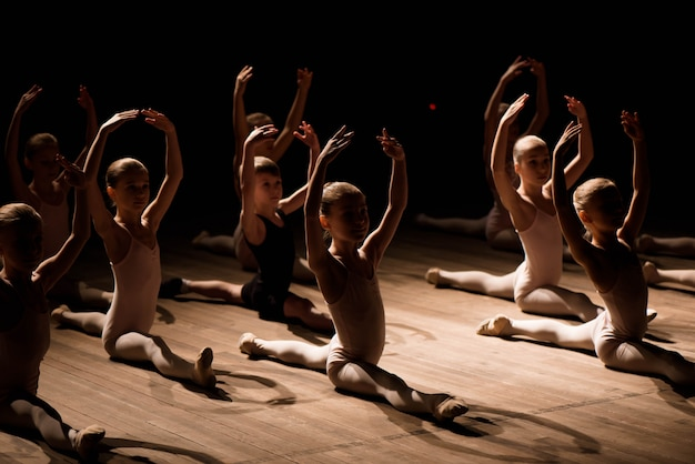Children doing splits while warming up on the stage