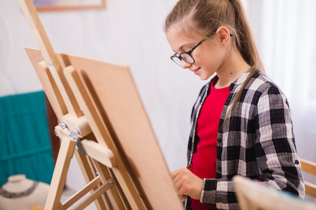 Children draw on an easel in art school.