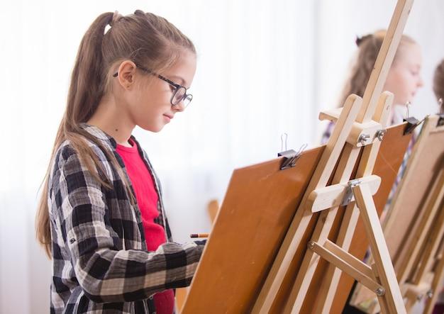 Children draw on an easel in art school.