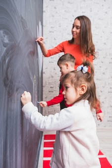 Children drawing on blackboard with teacher