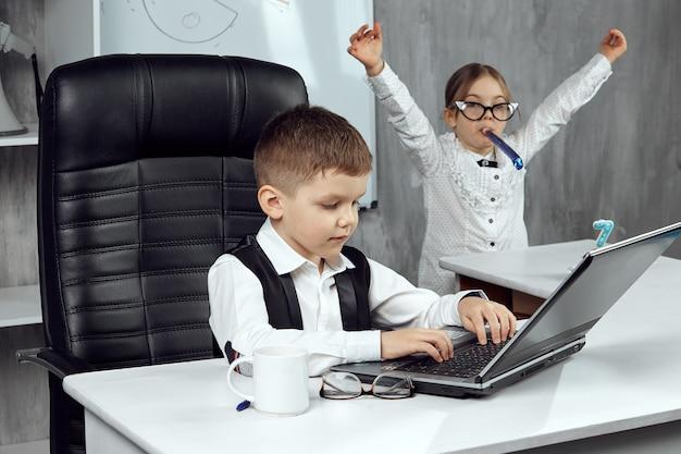 Дети в костюмах офисных работников празднуют седьмую годовщину компании. работники небольших офисов наслаждаются праздником. концепция праздника на работе. дети - хозяева.