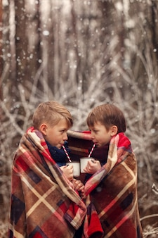 Children drink hot chocolate under warm blanket in winter forest. christmas vacation.