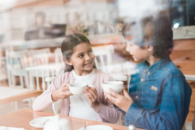 Children drink tea and have conversation in cafe.
