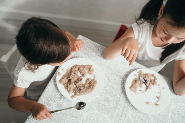 아이들은 아침 식사로 유제품이 없는 죽을 먹습니다. 먹는 아이들의 상위 뷰
