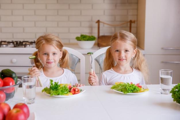 Children eat healthy food in the kitchen
