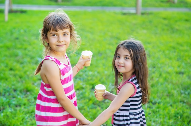 Children eat ice cream in the park.