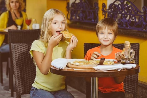 子供たちは屋外でピザを食べ、ジュースを飲む