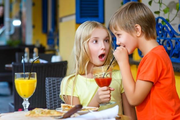 Дети едят пиццу и пьют сок на открытом воздухе