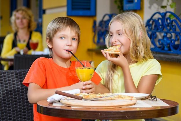 Children eat pizza and drink juice outdoor