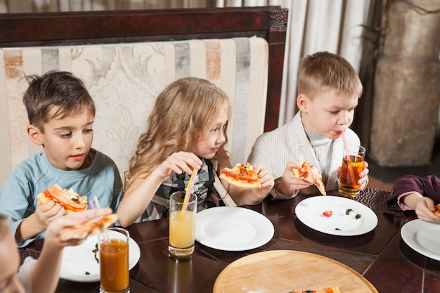Children eat pizza in a restaurant.