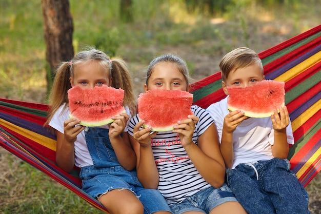 子供たちは、新鮮な空気の中で、ハンモックに座って、スイカと冗談を食べます