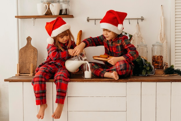 Дети едят рождественское печенье и пьют молоко