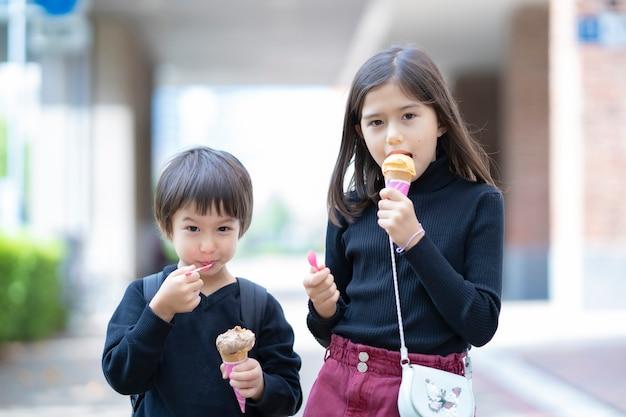 Дети едят мороженое кукурузного типа с ложкой