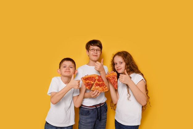 Children eating pepperony pizza on yellow background. unhealthy food concept.