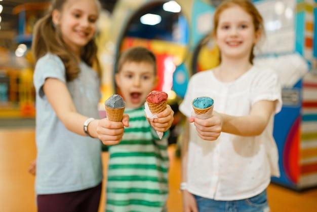 子供たちはエンターテインメントセンターでアイスクリームを食べます。休日の男の子と女の子のレジャー、子供の頃の幸せ、遊び場での幸せな子供たち