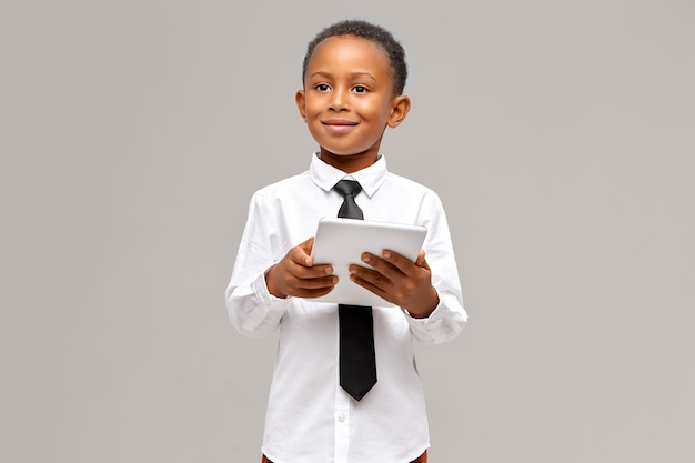 Children, electronic devices and gadgets concept. smart confident african pupil in uniform posing isolated with portable touch pad computer in his hands, surfing internet or shopping online