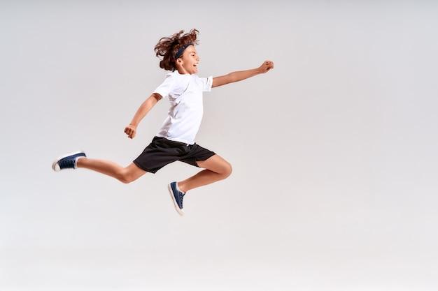 회색 배경 위에 고립되어 점프하는 10대 소년의 스포츠 전체 길이 샷에 종사하는 아이들