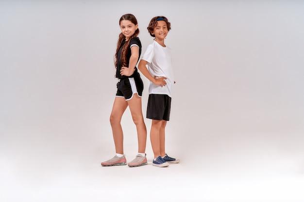 스포츠에 종사하는 어린이 두 명의 십대 귀여운 소년과 소녀가 카메라를 보고 운동복을 입고