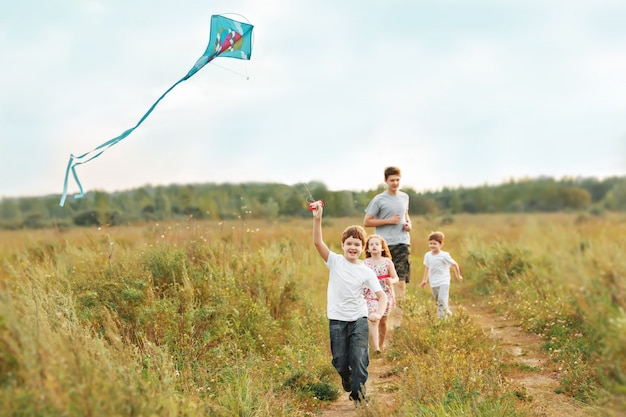 Children enjoy playing with a flying kite.