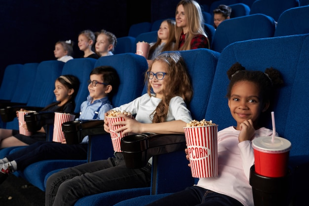 Children enjoying film premiere in movie theatre.