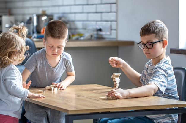 Children enthusiastically play a board game with wooden cubes on the table.