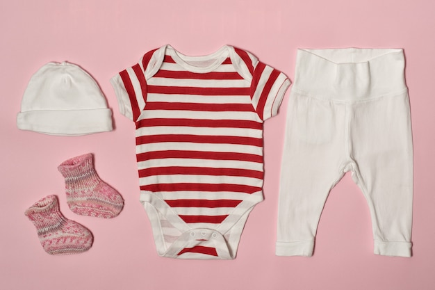 Children fashion  on a pink . cap, bodysuit, pants and socks.