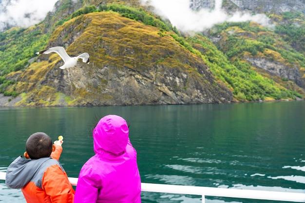 カモメに餌をやる子供たち、ソグネフィヨルド海クルーズ。
