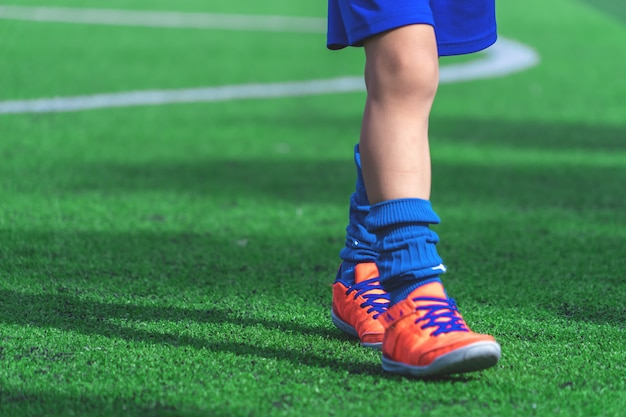 Children feet with soccer boots training on training cone on soccer ground