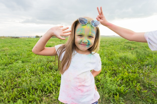 Children, festival of holi and holidays concept - happy little girl wearing sunglasses covered
