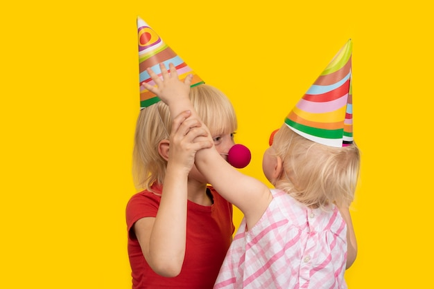 Children in festive hats and clown noses. children's holiday. birthday children.