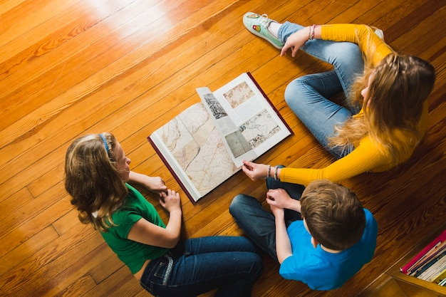Children on floor turning over book pages