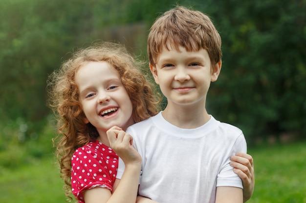 Children friends embracing in summer park.
