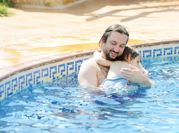 Дети весело играть с водой на летнем бассейне