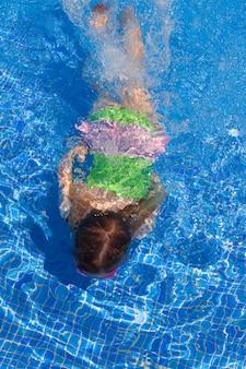 어린이 gilr 파란 수영장에서 수중 수영
