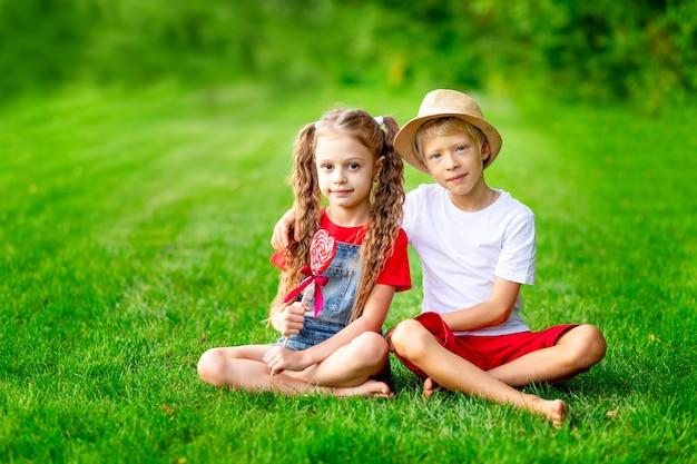 여름에 큰 롤리팝 심장을 가진 어린 소녀와 소년 금발은 녹색 잔디에 있는 잔디밭, 발렌타인 데이 휴가의 개념, 텍스트를 위한 공간