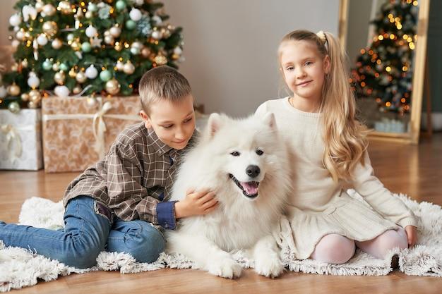 Дети девочка и мальчик с самоедской собакой на рождественской сцене