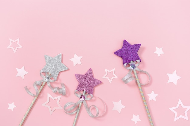 Children girl birthday party holiday background with bright stars and magic wand pink pastel colored.