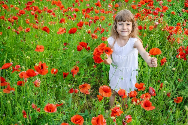 Children girl in a field with poppies.
