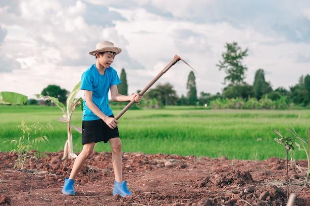 Дети девочка держит мотыгу и копает почву для посадки дерева в саду