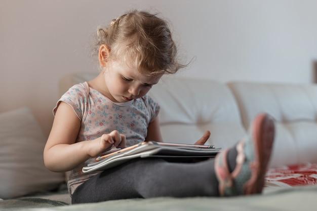 家の服を着た子供の女の子がソファに座り、タブレットで学びます。遠隔学習とガジェット