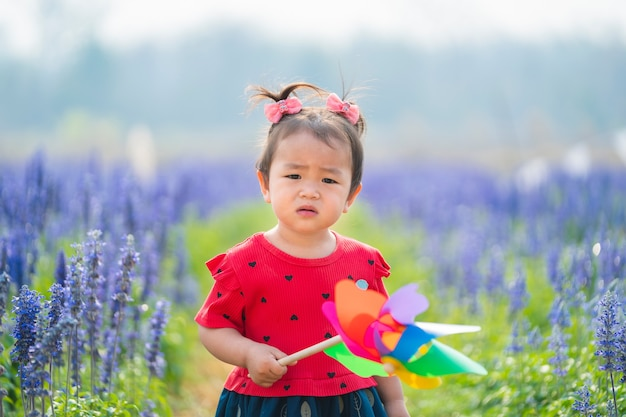 Children girl standing in flower garden and holding toy windmill looking at camera